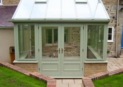 A green conservatory made of timber