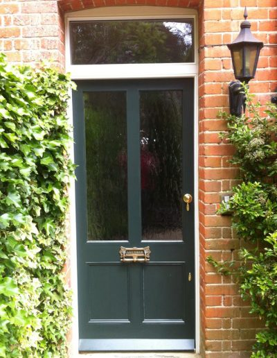 green front door with large windows