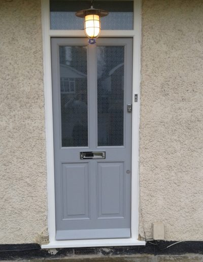 grey timber door with silver letterbox